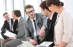 Employee with colleagues before the briefing. Employee of a company with colleagues to discuss working papers royalty free stock photography