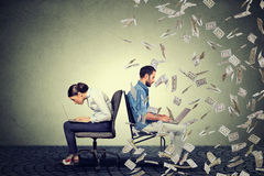 Employee compensation economy concept. Woman working on laptop sitting next to man under money rain. Stock Photo