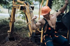 Employee concept. Employee flex biceps and triceps muscle. Strong employee at excavator cabin. Employee in working. Uniform on excavation site. Strength and royalty free stock images