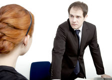 Employee confronting her boss. Rear view of a redheaded female employee confronting her male boss who is standing behind his desk looking at her with an Royalty Free Stock Photos