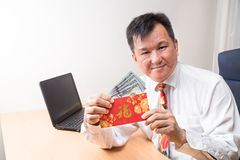 Employee displaying red packet with Good Fortune character in of Royalty Free Stock Photography
