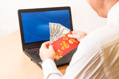 Employee displaying red packet with Good Fortune character in of Stock Images