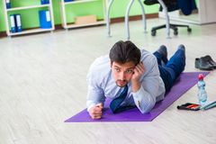The employee doing exercises during break at work Royalty Free Stock Image
