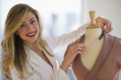 Employee Dressing Mannaquin In Clothing Store Royalty Free Stock Images