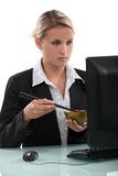 Employee eating at her computer Royalty Free Stock Photo