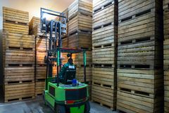 The employee on the electric forklift carry the container wiht r. Ipe apples to inside a fridge airless storage camera. Production facilities of grading, packing royalty free stock image