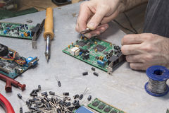 An employee at an electric service while at work. NRepair of computer hardware. Modem repair. Replacement of the capacitor Stock Images