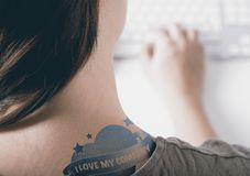 Employee Advocacy and Engagement. Woman working on a computer with close up on a tatoo with the text i love my company. Concept of employee advocacy, engagement stock photo