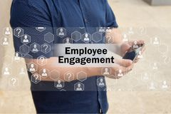 Employee Engagement   on the touch screen with a blur background of the businessman with the phone.The concept of Employee Engagem. Ent Stock Photos