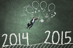 Employee flying over the number 2014 to 2015 Royalty Free Stock Images
