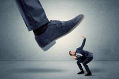 Employee getting trampled by big shoe. Demoralised employee symbolized by small man getting trampled royalty free stock images
