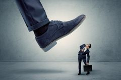 Employee getting trampled by big shoe. Demoralised employee symbolized by small man getting trampled stock photo