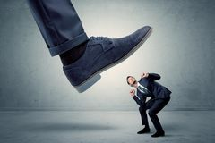 Employee getting trampled by big shoe Royalty Free Stock Image