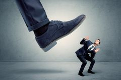 Employee getting trampled by big shoe. Demoralised employee symbolized by small man getting trampled royalty free stock photo