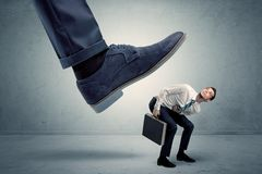 Employee getting trampled by big shoe. Demoralised employee symbolized by small man getting trampled royalty free stock photography
