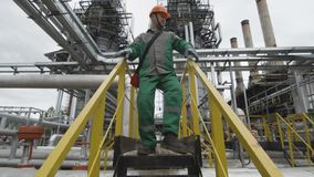 Employee Goes down Stairs among Petrol Pipelines