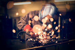 Employee grinding steel with sparks Royalty Free Stock Photography