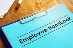 Employee handbook and clipboard on table stock photo