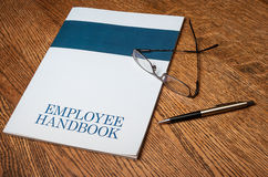 Employee handbook. Manual on a desktop with glasses and a mechanical pencil stock images