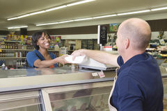 Employee Handing Product To Customer In Supermarket royalty free stock photography