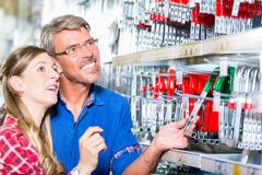 Employee of hardware store helping customer in ironware departme Royalty Free Stock Photo