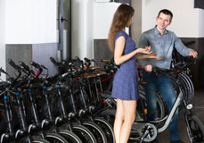 Employee helping adult guy to select bike at rental agency Stock Photos