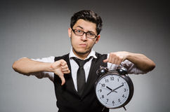 The employee holding alarm clock against gray Royalty Free Stock Photos