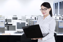 Employee holds laptop and standing in office Royalty Free Stock Photography