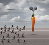 Employee Incentive. Business concept as a group of businessmen and businesswomen running on a track towards a dangling carrot on a moving cable as a financial Stock Photos