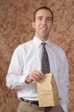 Employee Lunch. A young employee wearing a white shirt and tie, holding his paper bagged lunch Royalty Free Stock Photo