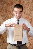 Employee Lunch Time. An employee wearing a tie is looking happy about what he sees in his paper lunch bag Stock Image