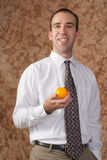 Employee With Orange. A smiling employee wearing a shirt and tie is holding an orange Stock Image