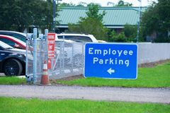 Employee Parking sign with arrow and parked cars behind fence Royalty Free Stock Photo