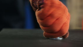 Employee at the plant twists the wing nut. Man at the plant twisting the wing nut on metallic surface closeup. The worker in orange gloves quickly tighten the stock video footage