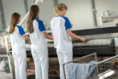 Employee the pressing. Employee women working on  the pressing textile Royalty Free Stock Photography