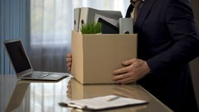 Employee putting his stuff from work desk in carton box, leaving job, retirement. Stock photo royalty free stock images