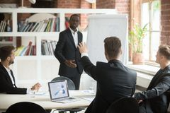 Employee raises hand to ask business coach a question. Employee raises hand to ask business coach a question during briefing. African american CEO consulting Stock Images
