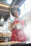 Employee in red apron holding box Royalty Free Stock Images