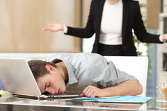 Employee sleeping with boss watching. Employee sleeping with the face over the laptop with his angry boss watching back at office Stock Image