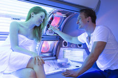 Employee in a solarium counseling customer or client at tanning bed Stock Photos