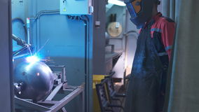 An employee in a special protective suit oversees the process works welding apparatus. Control the man behind the stock video footage