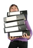 Employee with stacks of files. Employee carrying a heavy pile of documents Royalty Free Stock Images