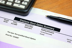 Employee Stock Option Summary. An employee stock option summary document on a wood table with a pen and calculator Royalty Free Stock Photos