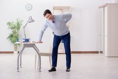 The employee suffering from backpain in office. Employee suffering from backpain in office Stock Photos
