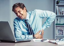 Employee suffers from severe pain in back. stock photo