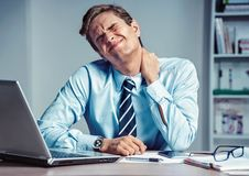 Employee suffers from severe pain in neck. Photo of man working in the office. Medical concept royalty free stock image