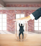 Employee trapped inside glass jar. Employee miniature trapped inside transparent glass jar by employer's hand. Red brick interior background royalty free illustration