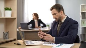 Employee typing message on cellphone, businessman working at desk, workspace royalty free stock photography