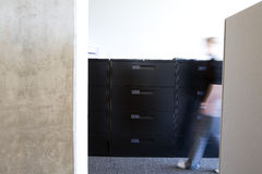 Employee walking in clean modern office. Motion blur of employee walking in a clean modern office. Employee is walking past a hallway in front of brand new Stock Photos