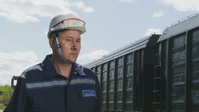 Employee Walks along Train and Looks around Slow Motion. KAZAN, TATARSTAN/RUSSIA - SEPTEMBER 12 2017: Slow motion employee in uniform walks along cargo train and stock video